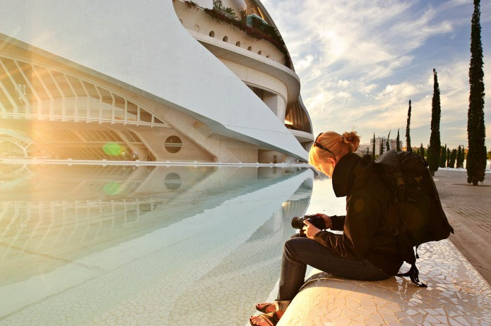 woman sitting in front of the Palau des Artes in Valencia