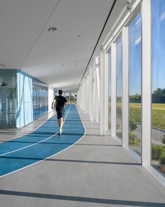 architectural photography of centennial college athletic centre in toronto - interior running track with runner