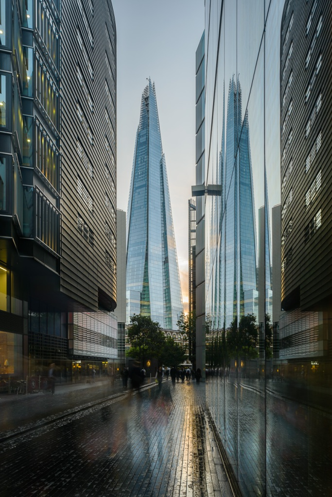 The shard reflected on a glass facade at sunset