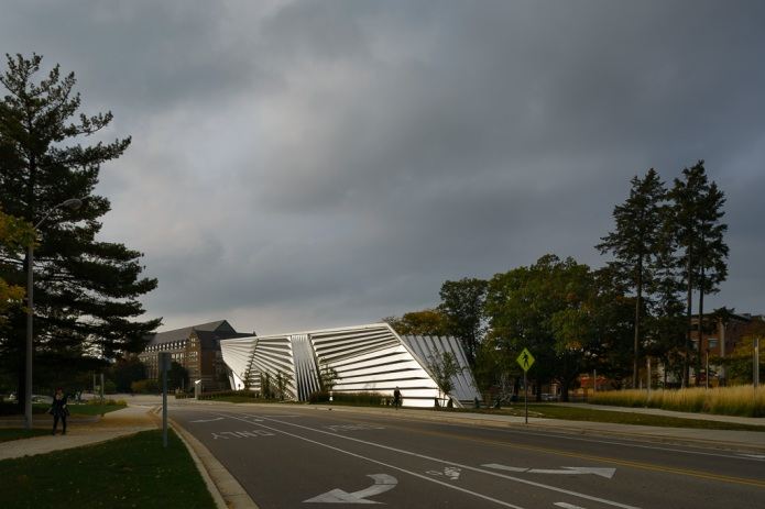 Stormy light glistens on the metal surface of the broad museum facade (Zaha Hadid Architects)