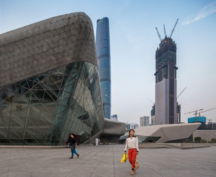 Young couple walking outside of the Guangzhou Opera House designed by Zaha Hadid