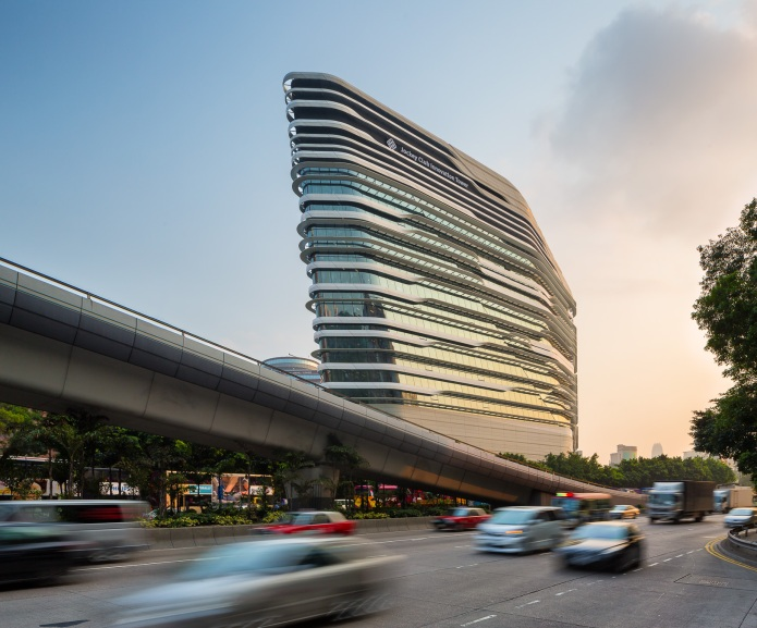 The sun sets as traffic goes by the Jockey Club Innovation Tower by Zaha Hadid Architects