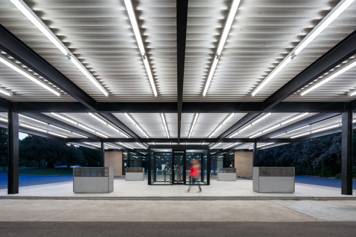 A person walks under the canopy at the converted Mies van der Rohe gas station