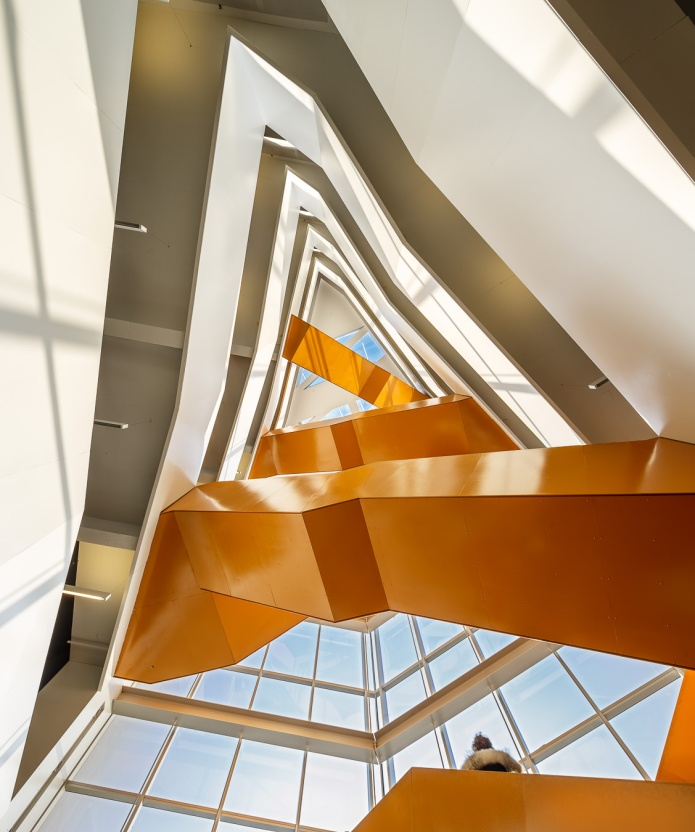 The vibrant orange central staircase is an architectonic symbol of the Gingko tree in the courtyard