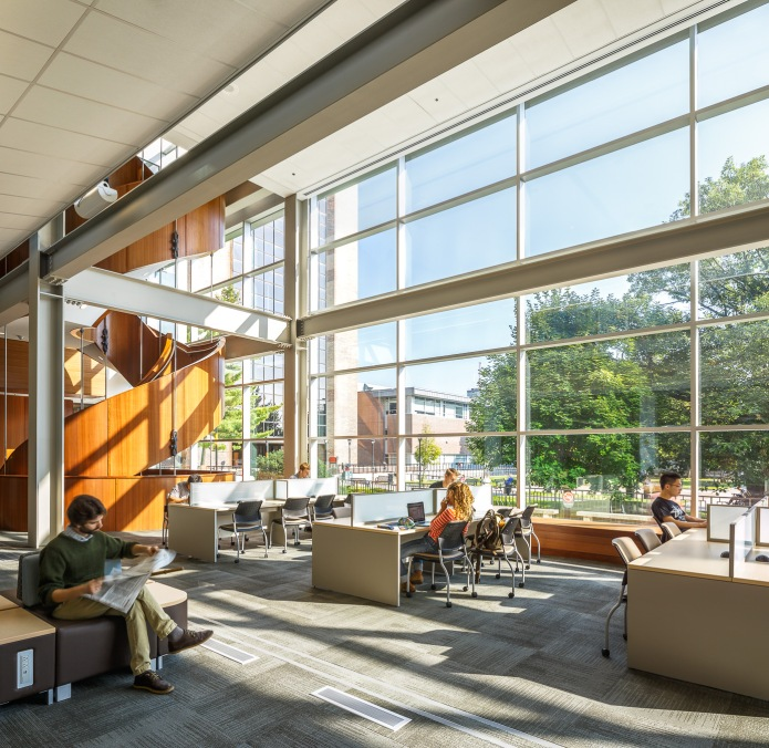 students in the double height reading room facing the Carleton Quad outside