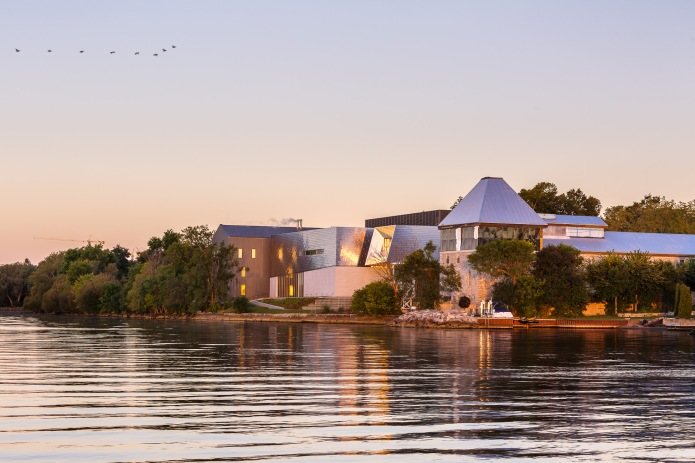 The Isabel Bader and Lett Centre seen from the water at sunrise. - Snohetta